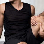 Therapist treating injured knee of athlete male patient in clinic